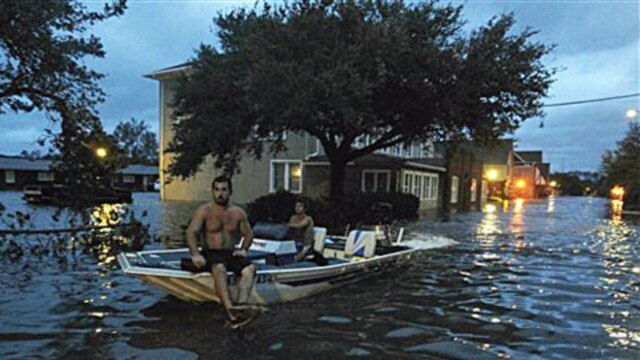 Two men use a boat on a flooded street in Manteo, North Carolina, after Hurricane Irene