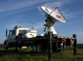 A NOAA mobile storm-chasing radar vehicles is deployed outside a bat cave at dusk.