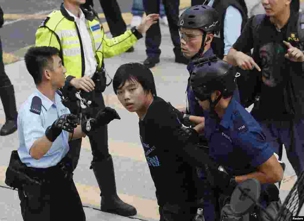 Police arrest a student protester after he refused to leave a the protest site at Mong Kok shopping district in Hong Kong, November 25, 2014.