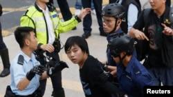 Polisi menahan seorang mahasiswa yang menolak meninggalkan jalan utama distrik Mongkok di Hong Kong (25/11).