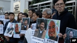 FILE - Pro-democracy activists hold pictures of Chinese activist Wu Gan (2nd-R) and other activists outside the Chinese central government's liaison office in Hong Kong, Dec. 27, 2017.