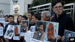 홍콩 민주화 운동가들이 27일 중국 연락사무소 앞에서 인권운동가 우간 등의 사진을 들고 석방을 촉구하는 시위를 벌이고 있다.