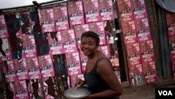 En Puerto Príncipe una mujer camina frente a carteles con propaganda de popular cantante Michel Martelly quien exigió que se realice otra ronda de votaciones.