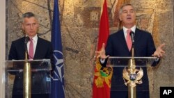 FILE - Montenegro's Prime Minister Milo Djukanovic, right, speaks and gestures after talks with NATO Secretary-General Jens Stoltenberg, in Podgorica, Montenegro.