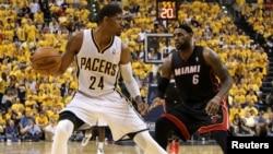 Le joueur-vedette des Indiana Pacers Paul George (24), à gauche, tente un drible face à LeBron James (6) de Miami Heat lors d'un match de basketball de la NBA, le 28 mars 2014.