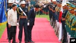 12일 필리핀을 방문한 아베 신조 일본 총리가 환영식에서 국기에 대해 예를 표하고 있다. 왼쪽은 로드리고 두테르테 필리핀 대통령.