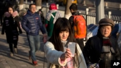 In this Feb. 28, 2016 photo, online web performer Wang Weiying, 18, broadcasts a live stream from her smartphone as she walks down a street in Beijing. Wang has turned to one live broadcast site, Huajiao, to earn money to study abroad. (AP Photo/Mark Schiefelbein)