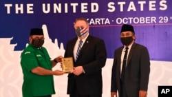 Menlu AS Mike Pompeo (tengah) menerima kenang-kenang dari Ketua Umum Pimpinan Pusat Gerakan Pemuda Ansor Yaqut Cholil Qoumas (kiri), didampingi Sekjen Nahdlatul Ulama, Yahya Cholil Staquf, di Nahdlatul Ulama, Jakarta, 29 Oktober 2020. (Adek Berry/Pool Photo via AP).