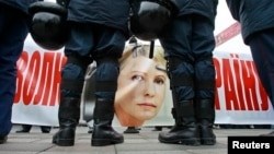 A banner with the portrait of jailed former prime minister Yulia Tymoshenko is seen as police stand guard during an opposition rally in front of the Parliament building in Kyiv, Nov. 13, 2013.