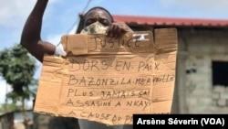 Un homme tient un panneau pour demander justice, à Nkayi au Congo-Brazzaville, le 30 septembre 2020. (VOA/Arsène Séverin)