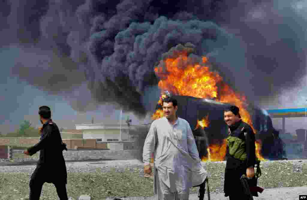 Pakistani security personnel are seen near a burning NATO supply oil tanker following an attack at Sor Kamar in the Khyber tribal district, some 25 kilometers west of Peshawar. At least two people were killed when gunmen in northwest Pakistan opened fire on tankers carrying fuel for NATO troops in Afghanistan.