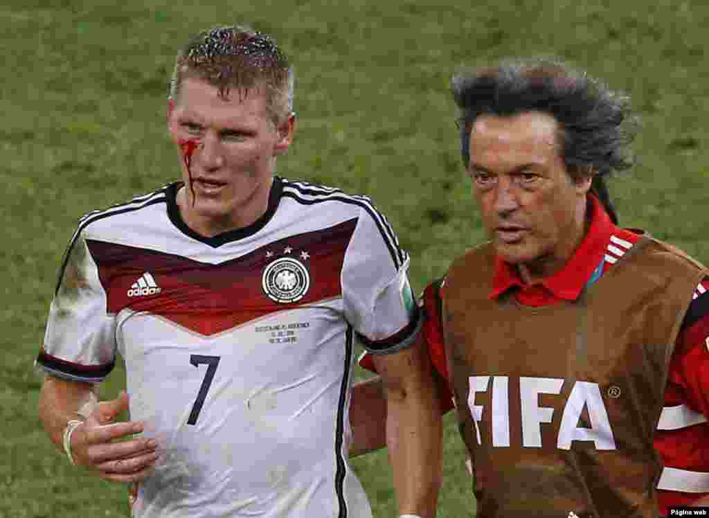 Germany's Bastian Schweinsteiger leaves the pitch after he was injured during extra time at the Maracana stadium in Rio de Janeiro, July 13, 2014.