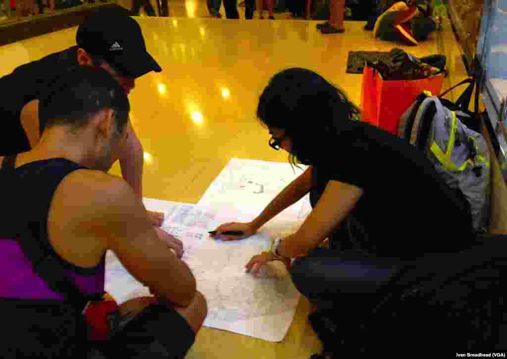 Inside the Admiralty metro station, a main transport hub for the occupation campaign, three teen-aged Occupy Central members pore over a crude map. They make up the evacuation team, responsible for planning an exit strategy for the tens of thousands of protesters who remain on site, should a police offensive cause another stampede, Hong Kong, Oct. 5, 2014.