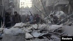 시리아 정부군이 4일 반군이 점령한 알레포 지역에 공습을 가한 후 마을 주민들이 폐허가 된 건물 잔해를 바라보고 있다.