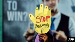 "Seorang aktivis mengikuti acara memperingati Hari Perempuan Sedunia di Banda Aceh, Aceh, 8 Maret 2019. Seorang pengunjuk rasa membawa spanduk bertuliskan ""Stop Bullying"". (Foto: AFP/Chaideer Mahyuddin)"