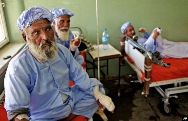 Afghan men, among nearly a dozen people who had their fingers cut off by Taliban fighters as a punishment for voting in this weekend's presidential runoff, rest in a hospital in Herat, Afghanistan, June 15, 2014.