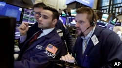 Trader Michael Milano, right, works with specialists Karan Virdi, center, and David Haubner, background, on the floor of the New York Stock Exchange, Jan. 9, 2018.