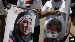 Two protesters carry posters with pictures of unidentified relatives in Syria, with the Syrian flag colors painted on their faces during an anti-Syrian regime rally near the Syrian embassy in Cairo, Egypt, July 5, 2011