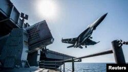Körfezdeki USS Carl Vinson uçak gemisinden havalanan bir F/A 18 savaş uçağı