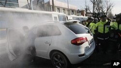 South Korean protester rams car into police bus guarding Chinese Embassy during rally to denounce Chinese fisherman, Seoul, Dec. 13, 2011.