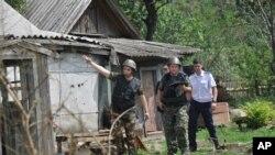 Anggota komite investigasi Rusia memeriksa sebuah rumah setelah mortir ditembakkan di kota Rusia, Donetsk, Minggu, 13 Juli 2014.