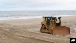 Una topadora en la playa Mantoloking, Nueva Jersey, lleva a cabo la reposición de arena en una área azotada por la supertormenta Sandy en 2012.
