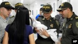 Policías colombianos llevan al hospital a una recién nacida abandonada descubierta junto a un auto cerca de un estadio en Cúcuta, Colombia. Una nota encontrada junto a la bebé dice que la niña se llama Ángela y que la madre no tiene medios para cuidarla. Foto AP, cortesía de la Policía Nacional de Colombia.