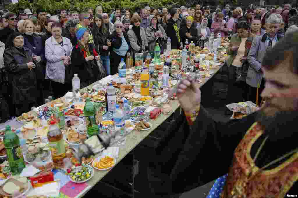 Local residents gather for an Orthodox ceremony to mourn the deaths of pro-Russian supporters killed recently in the Black Sea port of Odessa, Ukraine, May 10, 2014.