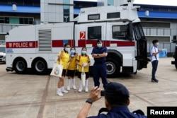 """在""""全民国家安全教育日""""展览当中,小学生在警察水炮车旁边拍照"""