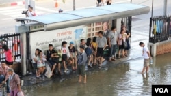 Para warga Bangkok yang mengungsi di bandara Don Muang sedang menunggu bis yang akan mengangkut mereka ke tempat lain yang lebih tinggi (25/10).