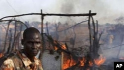 A policeman walks past the smoldering remains of a market in Rubkona near Bentiu in South Sudan, April 23, 2012.