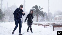 People walk in the snow, in the historic Sultanahmet district in Istanbul, Jan. 7, 2017. Heavy snow clogged roads, shipping traffic in Bosphorus and forced hundreds of flight cancellations in the Turkish metropolis.