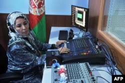 FILE - A female Afghan journalist is seen working at a radio station in Herat, Afghanistan, Oct. 14, 2012. The rising insecurity in Afghanistan has reportedly led to a decrease in the number of female journalists working and reporting on women's issues in the country.