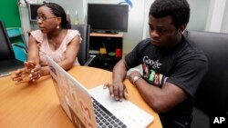 In this photo taken on Sept.13, 2012, Affiong Osuchukwu discusses Google service in Nigeria for mobile phone users to access emails through text messaging. (AP Photo/Sunday Alamba)
