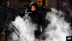 Una mujer protegida contra el frío camina en una manaña de otoño por Filadelfia, el miércoles 13 de noviembre de 2019. Una ola de frío polar avanza del centro-oeste del país hacia la costa este, rompiendo récords de sur a norte. AP/Matt Rourke.