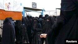 2019年3月31日,霍尔营地的伊斯兰国妇女排队领取物资
