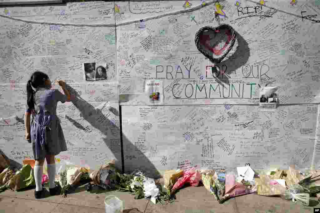 A school girl writes a message of support on a wall for the victims and those affected by the massive fire at Grenfell Tower in London.