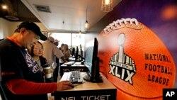 Ron, kiri, dan Tammy Chu, dari Boston, melihat peta tempat duduk setelah mengambil tiket Super Bowl mereka, 31 Januari 2015, di Phoenix, Arizona.