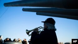 Bugler Nan LaCorte play taps during a ceremony commemorating the anniversary of the Dec. 7, 1941 Japanese attack on Pearl Harbor, on board The Battleship New Jersey Museum and Memorial in Camden, N.J., Thursday, Dec. 7, 2017.