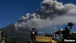 Seorang pria menggendong anaknya di kebun jagung desa Sibintun, kabupaten Karo, Sumatera Utara, dengan latar belakang asap dari Gunung Sinabung. (Foto: Dok)