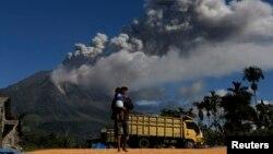 Seorang pria di desa Sibbintun distrik Karo nampak menggendong anaknya sambil berjalan di ladangnya yang kerning, sementara gunung Sinabung kembali mengeluarkan asap dan gas (25/11).