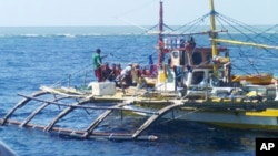 FILE - In this photo provided by Renato Etac, Chinese Coast Guard members, wearing black caps and orange life vests, approach Filipino fishermen as they confront them off Scarborough Shoal in the South China Sea.