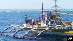 지난해 9월 필리핀 북서부 남중국해 스카버러 암초 주변에서 검은색 모자와 주황색 구명조끼를 입은 중국 해안경비대원들이 필리핀 어선에 물러날 것을 요구하고 있다. (자료사진)