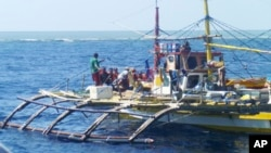 FILE - In this photo provided by Renato Etac, Chinese Coast Guard members, wearing black caps and orange life vests, approach Filipino fishermen as they confront them off Scarborough Shoal at South China Sea in northwestern Philippines, Sept. 23, 2015.