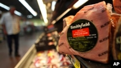 FILE - A Smithfield ham is seen in a grocery store in Richardson, Texas. Chinese meat processor Shuanghui International Holdings Ltd. agreed Wednesday, May 29, 2013, to buy Smithfield Foods Inc. for approximately $4.72 billion.