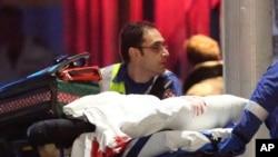 在悉尼劫持人质事件中,急救人员将带有血迹的担架送上救护车。