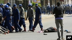 FILE: A woman lies in the road after being injured by police during protests in Harare, Friday, Aug, 16, 2019. (AP Photo/Tsvangirayi Mukwazhi)