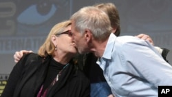 """FILE - Carrie Fisher, left, and Harrison Ford kiss at the Lucasfilm's """"Star Wars: The Force Awakens"""" panel on day 2 of Comic-Con International in San Diego, Calif."""