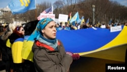 A woman in Washington sings Ukraine's national anthem while holding the national flag during a 2014 protest against Russia's aggression in Ukraine.