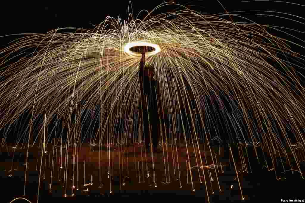 Seorang pria Malaysia membakar kembang api untuk menyambut Idul Fitri di Shah Alam, di luar Kuala Lumpur.